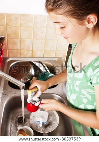 Teenage girl washing dishes in her kitchen - stock photo