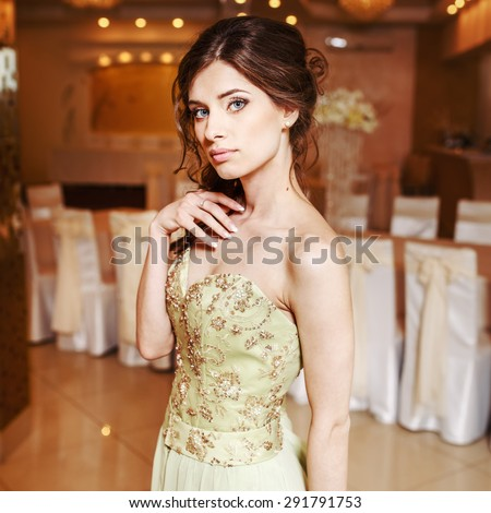 Teenage girl wearing fancy prom dress, posing on  school-leaving party.  - stock photo