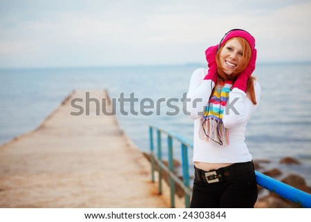 Teenage girl wearing warm clothing listening to music near the sea - stock photo