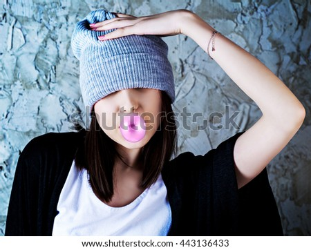 teenage girl with a bubble gum against old wall - stock photo