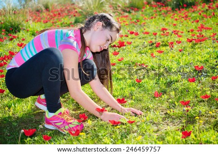 Teenage girl with braces on her teeth in a field of wild red anemone coronaria (windflower)  flowers blooming in the Galilee, Israel, after the winter rains - stock photo