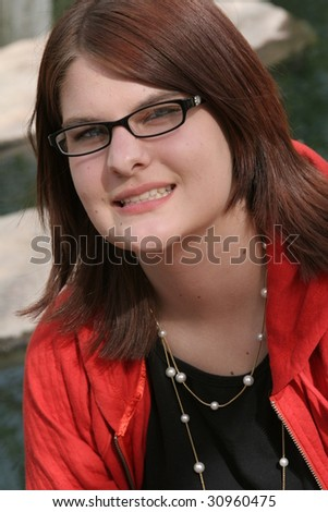 Teenage girl with glasses smiling by a rocky stream - stock photo