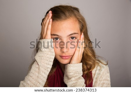 Teenage girl with hands on her face - stock photo