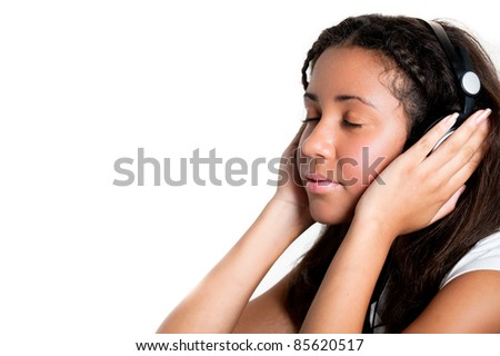 teenage girl with headphones and eyes closed, listening to music with hands over ears - stock photo
