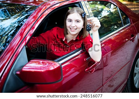 Teenage girl with her driver's license driving a new car and holding keys.   - stock photo