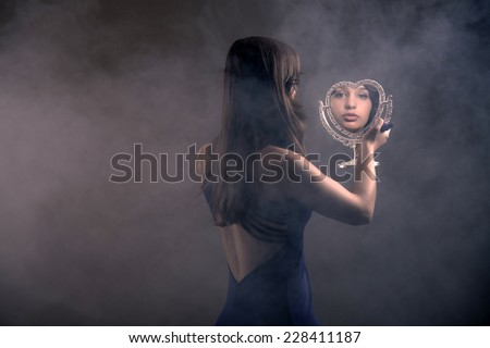 Teenage girl with long brown hair doing mascara and holding little mirror. Over the shoulder shot. - stock photo