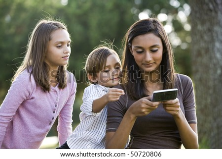 Teenage girl with mobile phone texting while younger siblings watch - stock photo