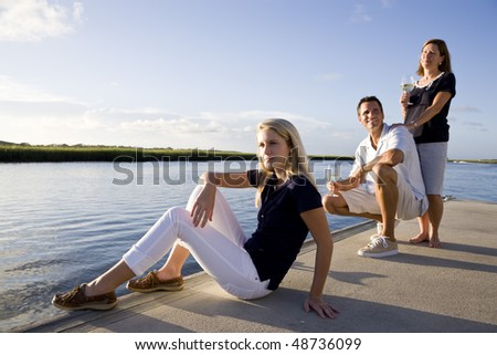 Teenage girl with parents on dock by water relaxing on sunny day - stock photo