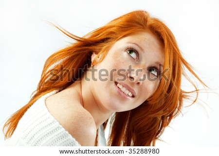 Teenage girl with red hair and green eyes looking up isolated on white studio background - stock photo