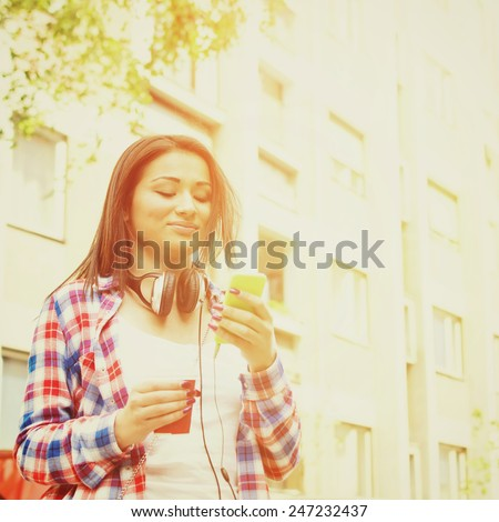 Teenage girl with smartphone and coffee outdoors. Gorgeous mixed race young woman in checkered shirt with headphones smartphone and takeaway coffee. Square format, instagram look filter. - stock photo