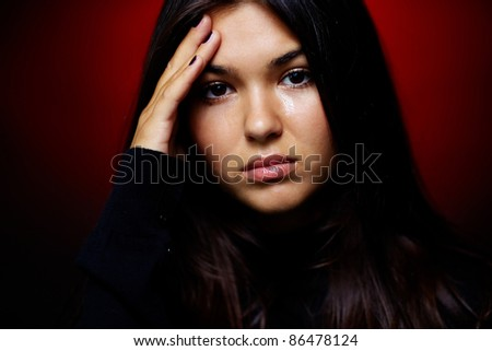 Teenage girl with wet eyes looking at camera - stock photo