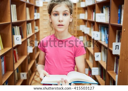 Teenage girl with wide open eyes stands holding book between bookcases in libray. - stock photo