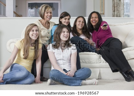 Teenage girlfriends at home with family on a sofa - stock photo