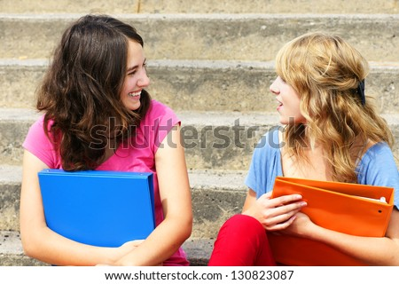 Teenage girlfriends talking and laughing at school - stock photo