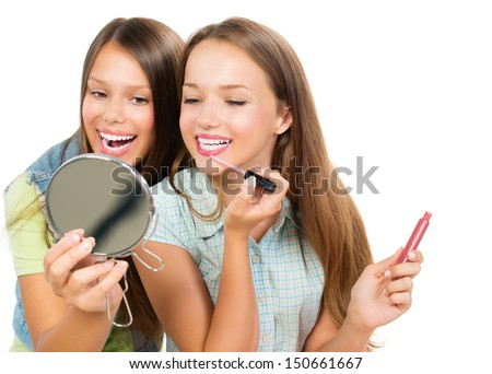 Teenage Girls Applying Make up and Looking in the Mirror. Pretty Teens Having Fun and Putting Makeup Lipstick or Lip gloss. Joyful Teenagers Isolated on a White Background. Cosmetics - stock photo
