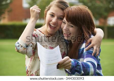 Teenage Girls Celebrating Good Exam Result - stock photo