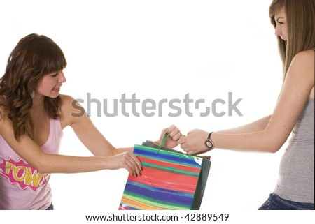 Teenage girls fighting over a shopping bag - sale madness - stock photo
