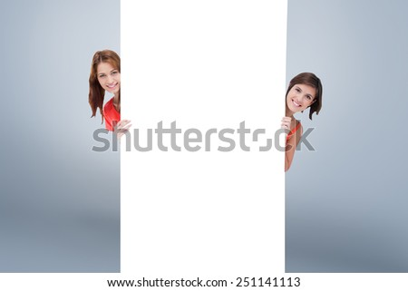 Teenage girls hiding behind a blank poster while showing their head from each side against grey vignette - stock photo