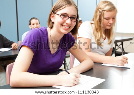 Teenage girls in high school class.  Real people. - stock photo