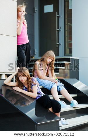 Teenage girls relaxing on a shop steps - stock photo