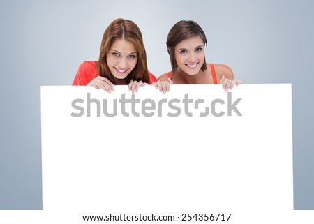 Teenage girls smiling while holding a blank poster and hiding behind it against grey vignette - stock photo