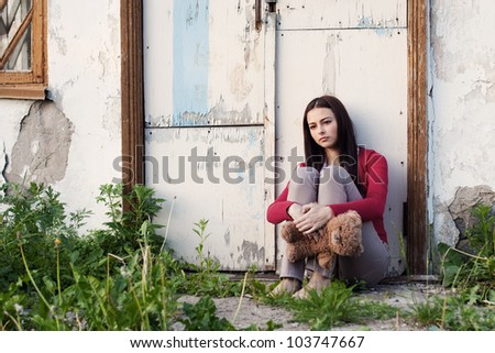 Teenage girls with toy on background old wall - stock photo
