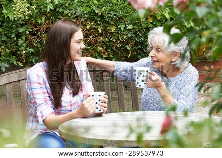 Teenage Granddaughter Relaxing With Grandmother In Garden - stock photo