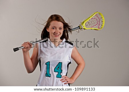 Teenage high school lacrosse player with her stick over her shoulder as she looks into the camera. - stock photo