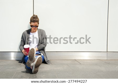 teenage laughing while look down by the glass wall with caffe cup - stock photo