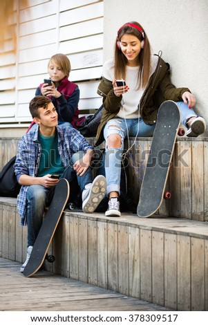 Teenage males and their smiling girlfriend relaxing with mobile phones outdoor