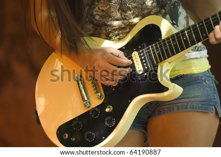 Teenage rocker standing on large rocks and sand - stock photo