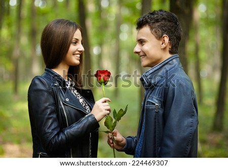 Teenage romance - a boy giving a flower to his girlfriend, outdoor in the park - stock photo
