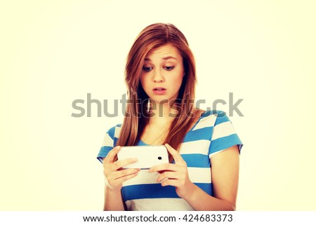 Teenage shocked woman reading a message on mobile phone - stock photo