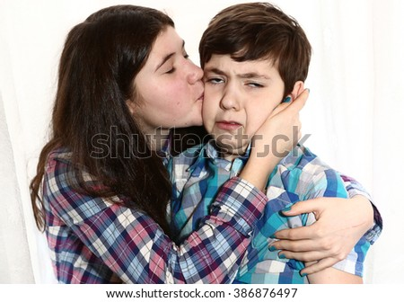 teenage siblings brother and sister with long brown dark hair in scottish shirt hug kiss close up portrait isolated on white - stock photo