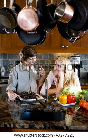 Teenage sister and brother together in kitchen talking - stock photo