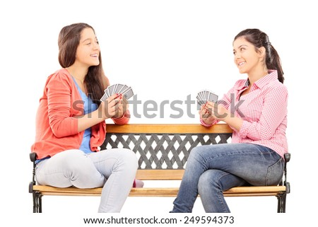 Teenage sisters playing cards seated on a wooden bench isolated on white background - stock photo