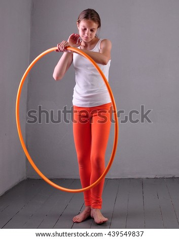 Teenage sportive girl is doing exercises with hula hoop grey background. Having fun playing game hula-hoop. Sport healthy lifestyle concept. Teenager exercising with tool. - stock photo