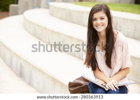 Teenage student working outdoors - stock photo