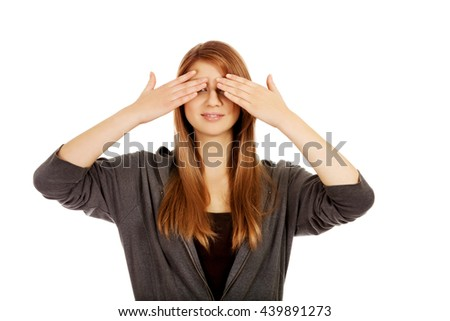 Teenage woman covering her eyes with both hands - stock photo