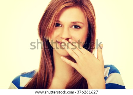 Teenage woman giggles covering her mouth with hand - stock photo