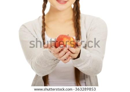 Teenage woman holding an apple. - stock photo
