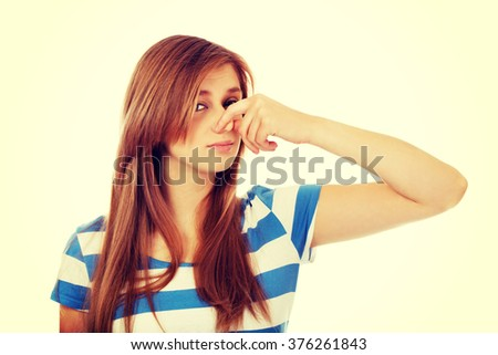 Teenage woman holding her nose because of a bad smell - stock photo