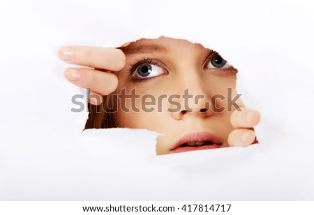 Teenage woman peeping through hole on paper - stock photo