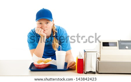 Teenage worker in a fast food restaurant bored and leaning on the counter.  White background. - stock photo