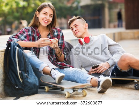 Teenager and his girlfriend with smartphones outdoors  - stock photo