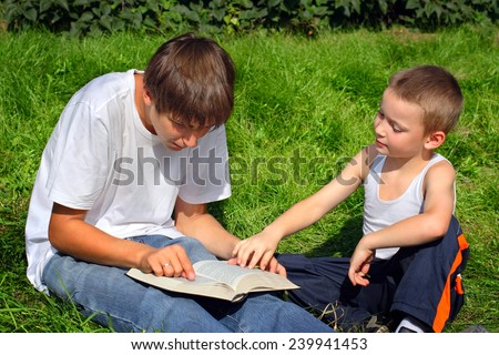 teenager and kid with a book on a summer meadow - stock photo