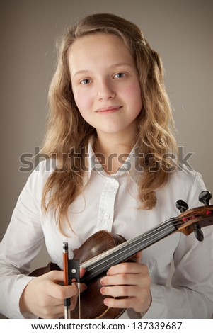 Teenager and violin, gray background - stock photo