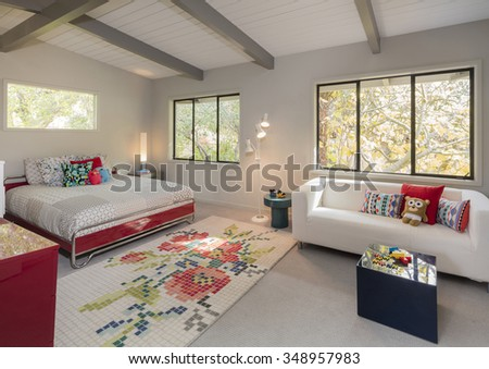 Teenager bedroom / kids room with light colorful decoration, rug, bed, pillows in red decoration. - stock photo