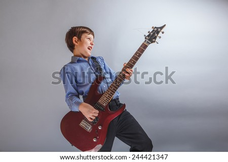 teenager boy brown hair European appearance playing guitar, happy on a gray background - stock photo