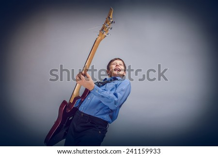teenager boy brown hair of European appearance playing guitar feels joy on a gray background cross process - stock photo